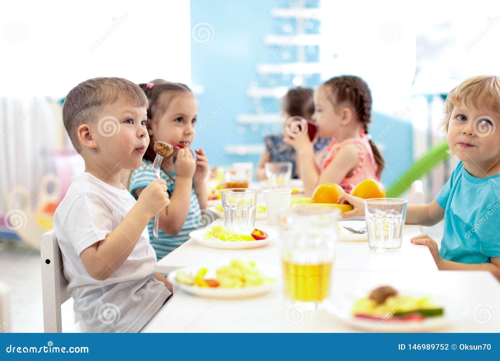 As crian?as t?m um almo?o no centro de guarda Crian?as que comem o alimento saud?vel no jardim de inf?ncia