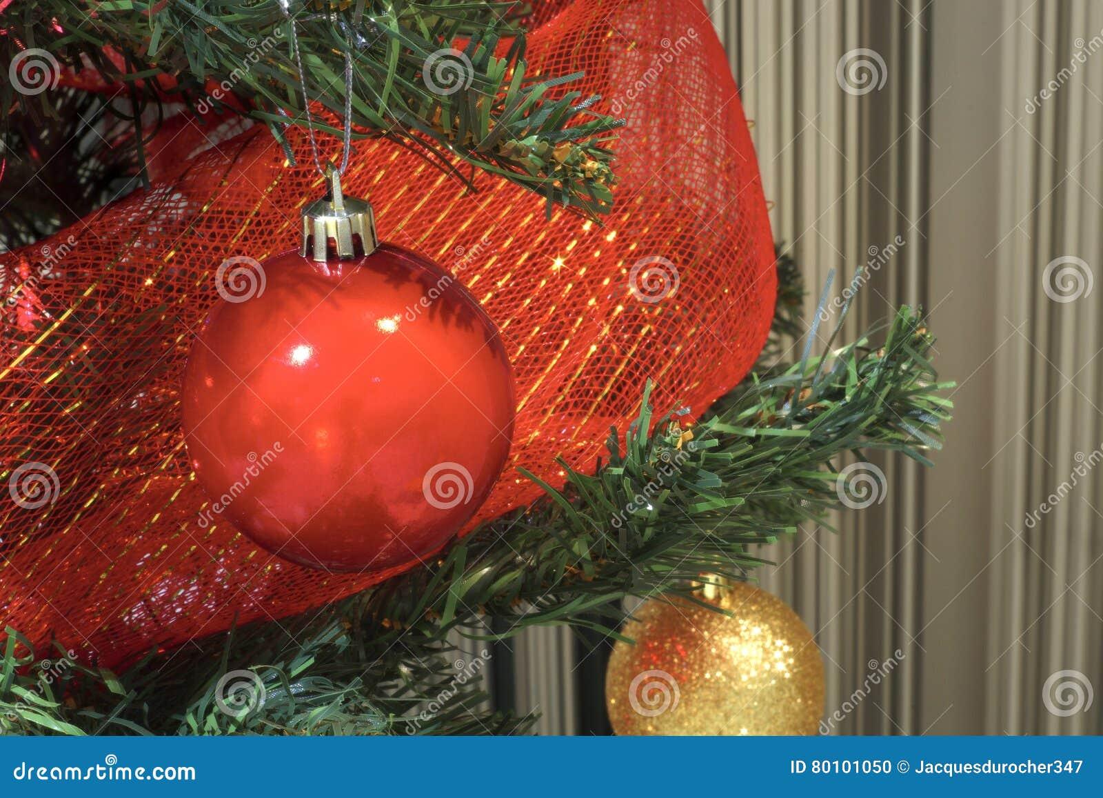 As decorações do Feliz Natal cardam bolas e fitas das quinquilharias em uma árvore