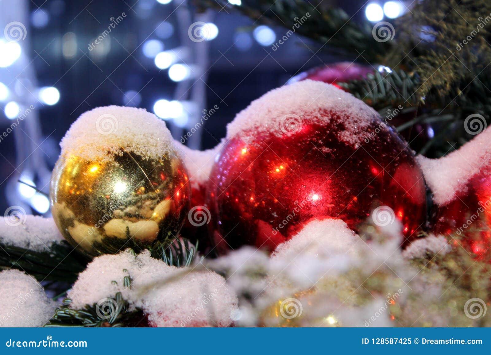 As decorações do Natal na árvore de Natal no vermelho e no ouro colorem espalhado com luzes, close-up