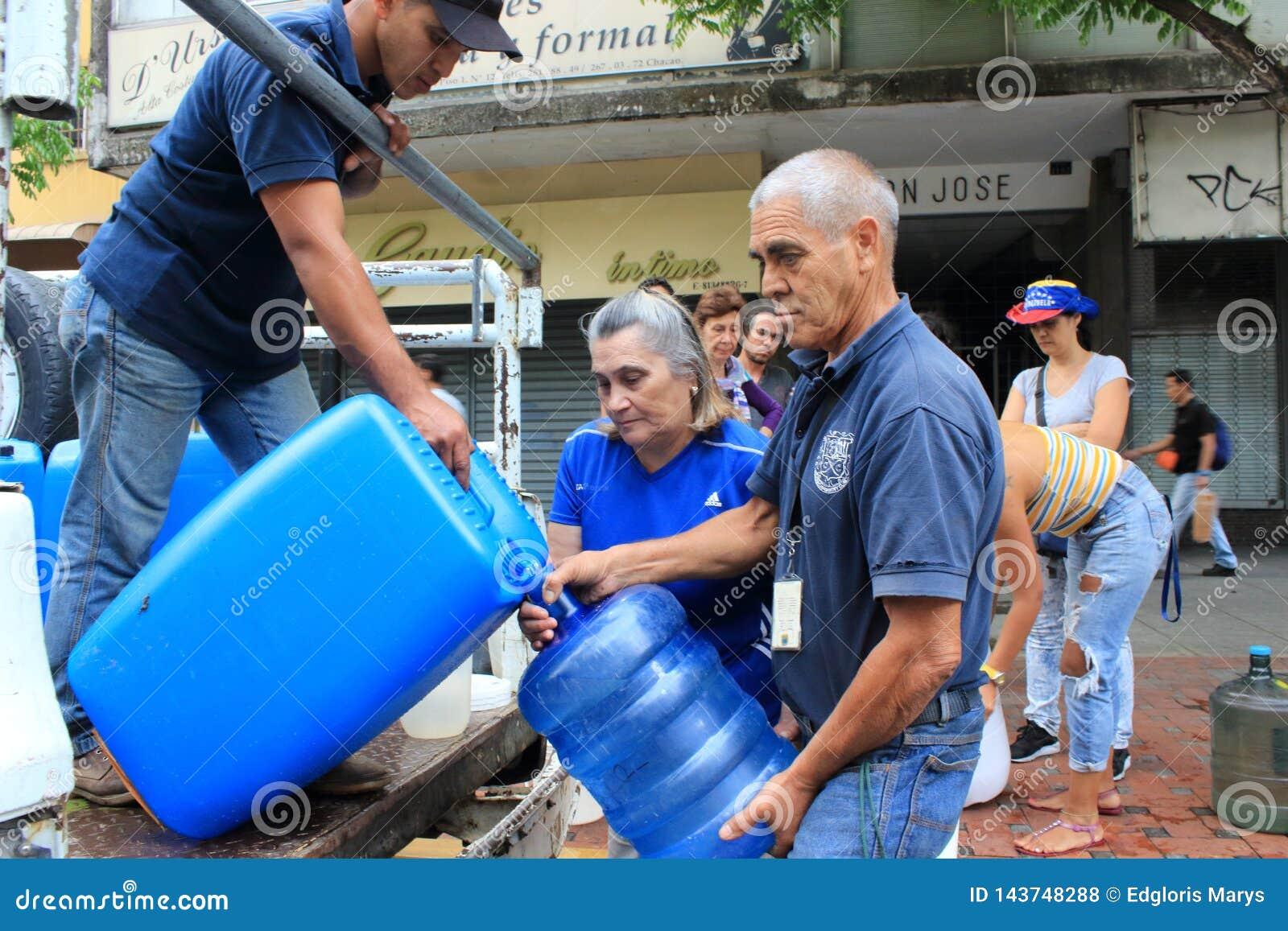 As famílias recolhidas acima das garrafas plásticas para enchê-las com os hosepipes molham em Caracas, Venezuela