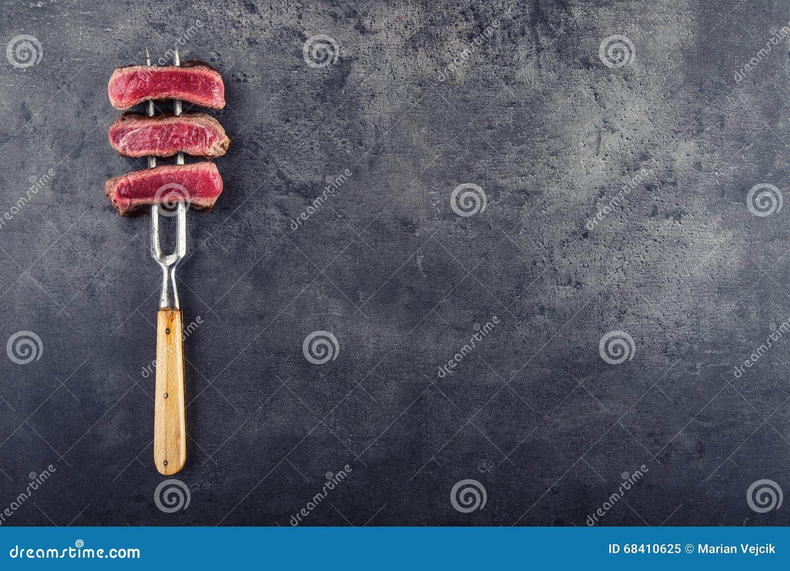 As fatias de bife do lombo na carne bifurcam-se no fundo concreto