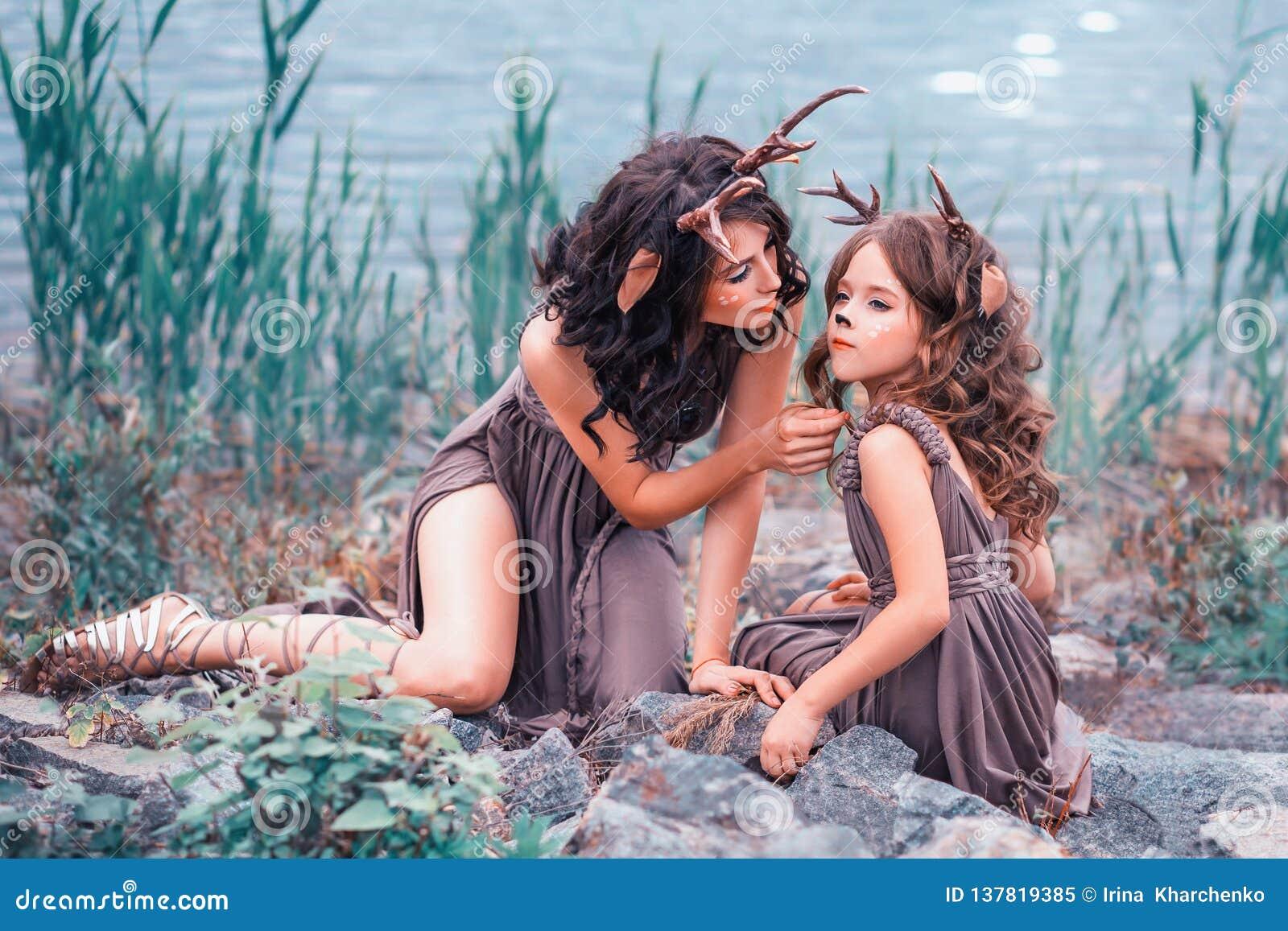 As faunas mãe e criança estão sentando-se nas rochas no banco do rio, o pai ocupam de seu bebê, meninas