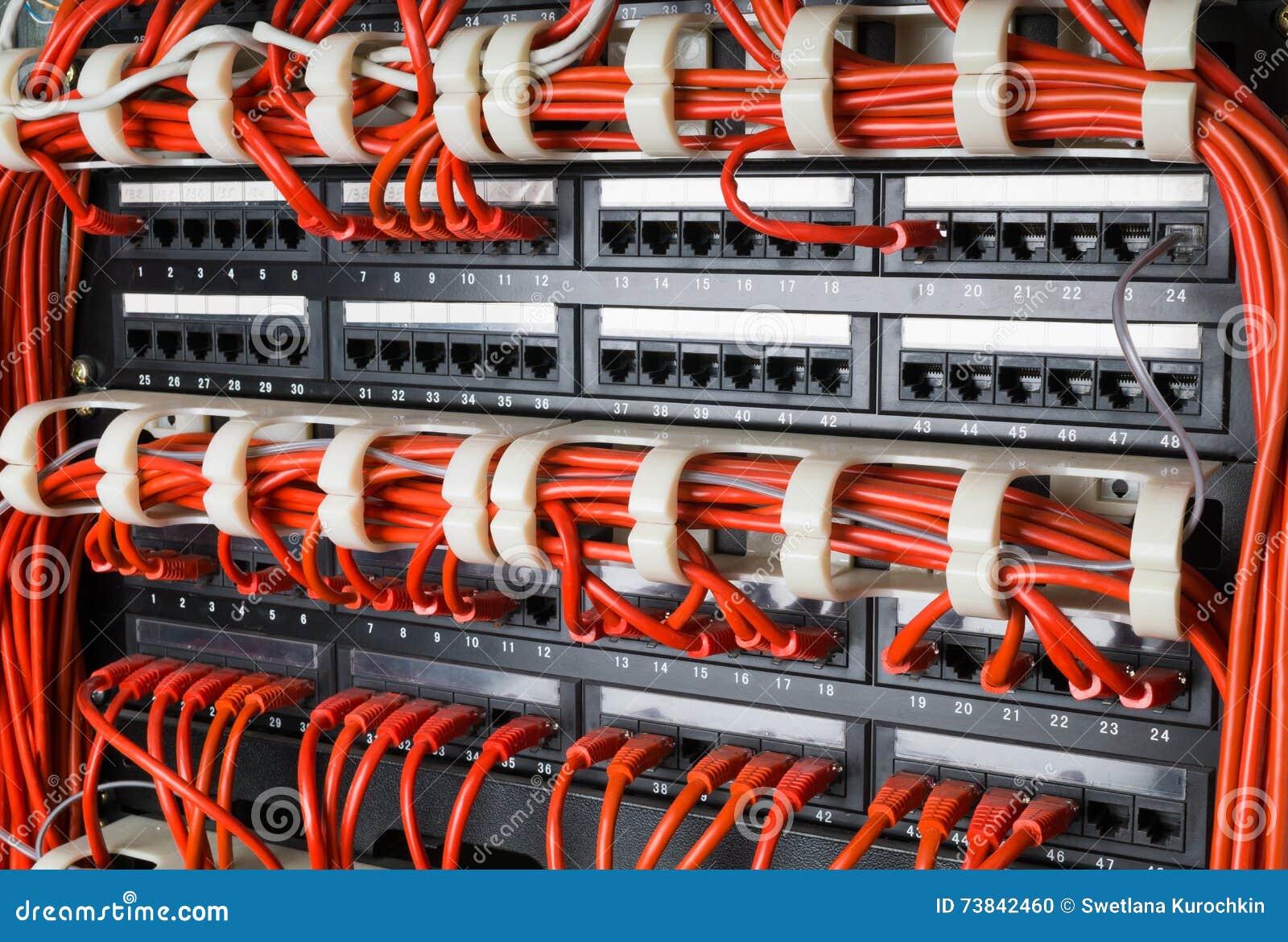 As fileiras de cabos da rede conectaram ao cubo do roteador e do interruptor