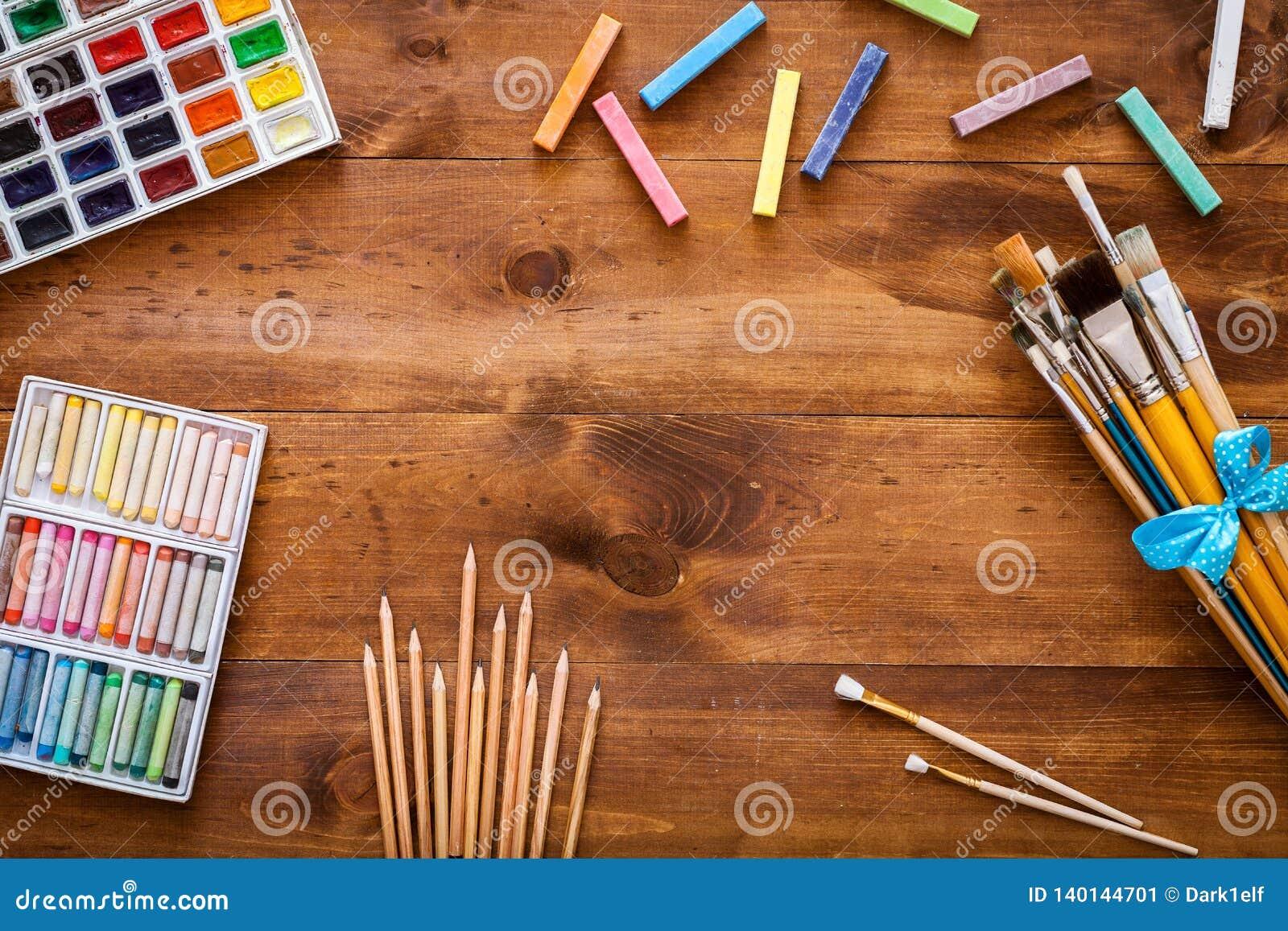 As fontes criativas ajustadas na mesa desarrumado, escovas das ferramentas dos acessórios do trabalho de arte de pintura, aquarel