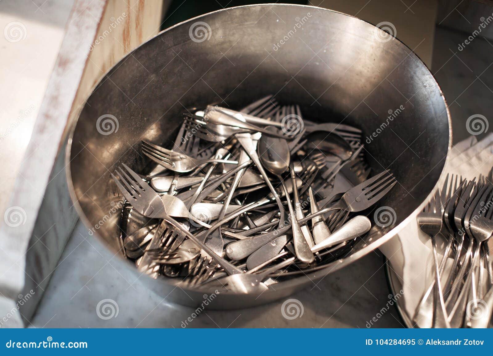As forquilhas e as colheres da tabela lavaram em uma bacia