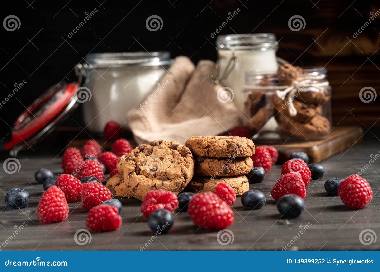 As framboesas, os mirtilos e as cookies no foco, no leite e na farinha selaram frascos no fundo