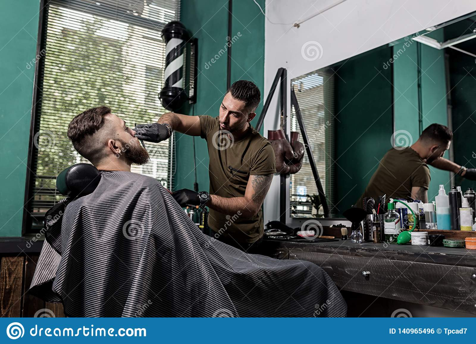 As guarnições do barbeiro com a barba das tesouras do homem novo brutal sentam-se na cadeira na frente do espelho em um barbeiro