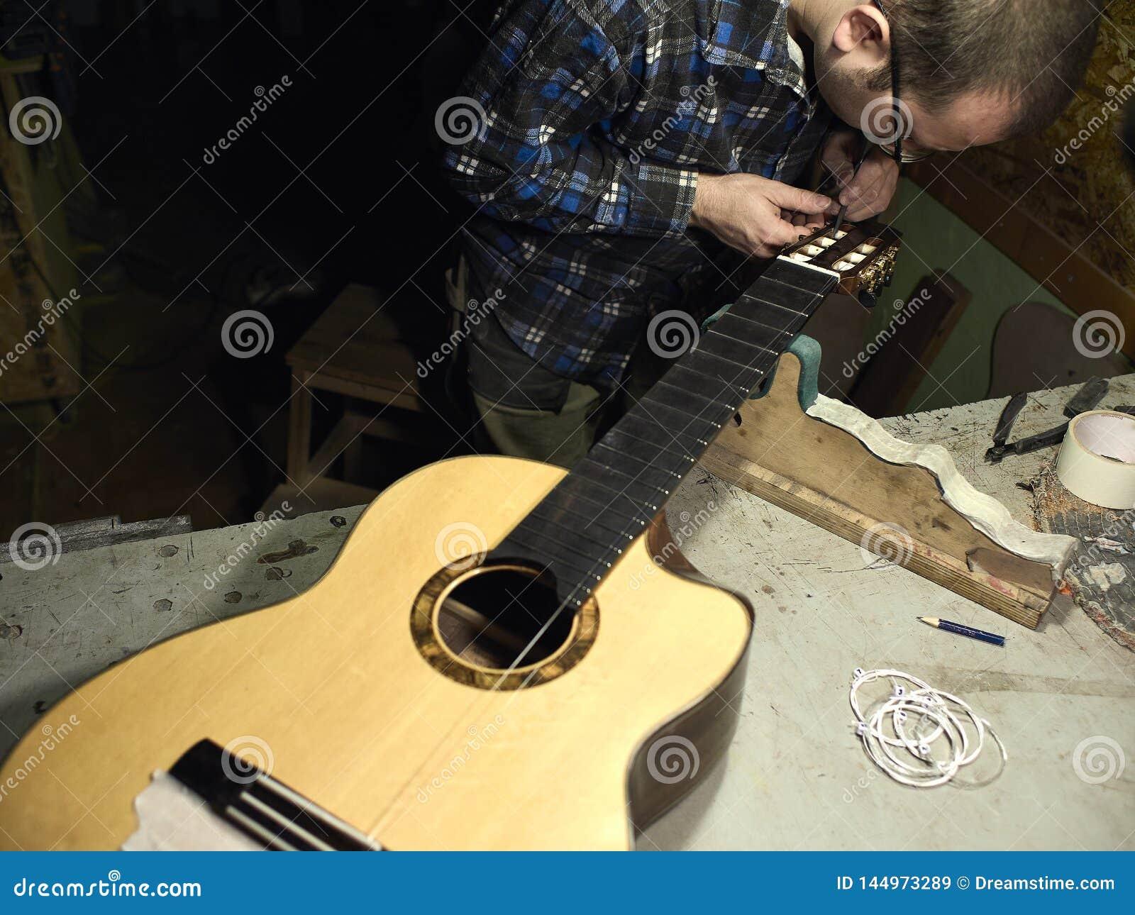 As guitarra Luthiers ajustam as cordas em uma guitarra