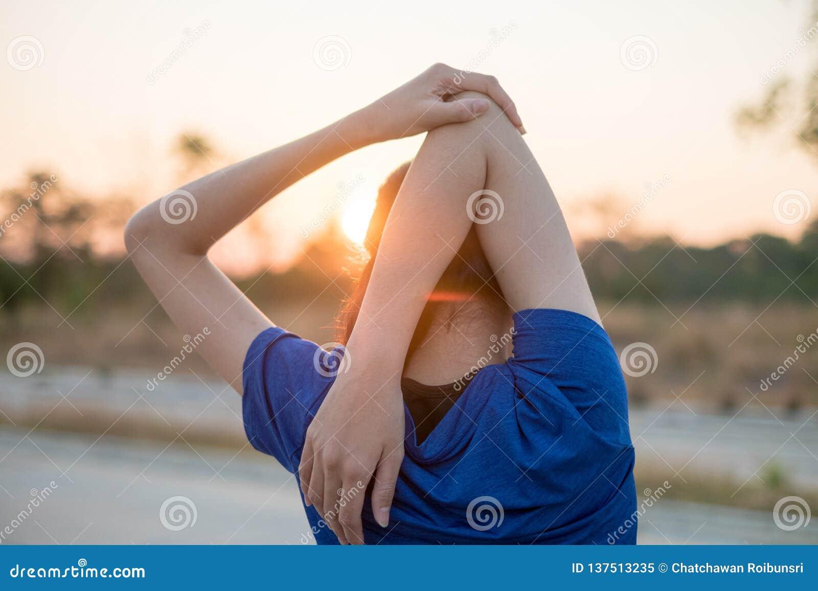 As jovens mulheres exercitam antes de exercitar no parque Esticou seus braços para o exame físico com o fundo do sol