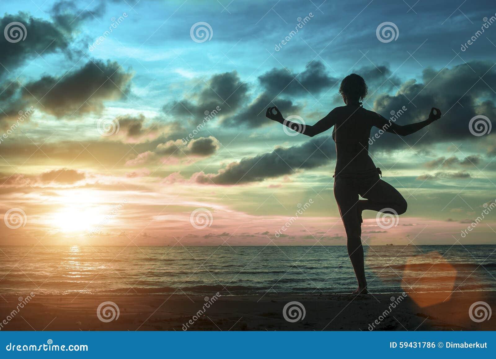 As jovens mulheres que estão na ioga levantam na praia durante um por do sol surreal surpreendente
