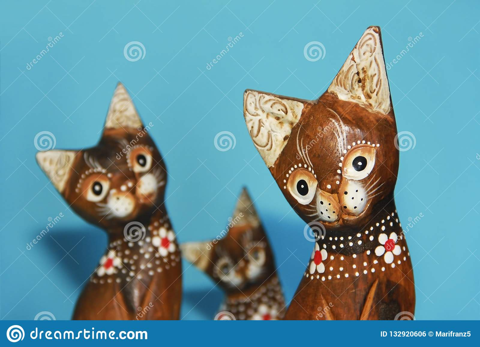 As lembranças marrons de madeira do gato sentam-se em um fundo azul