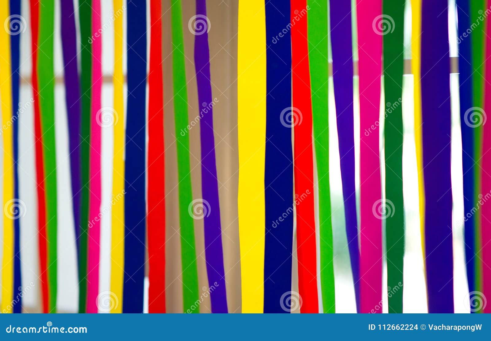 As listras de papel coloridas penduram na janela com backgr da luz natural