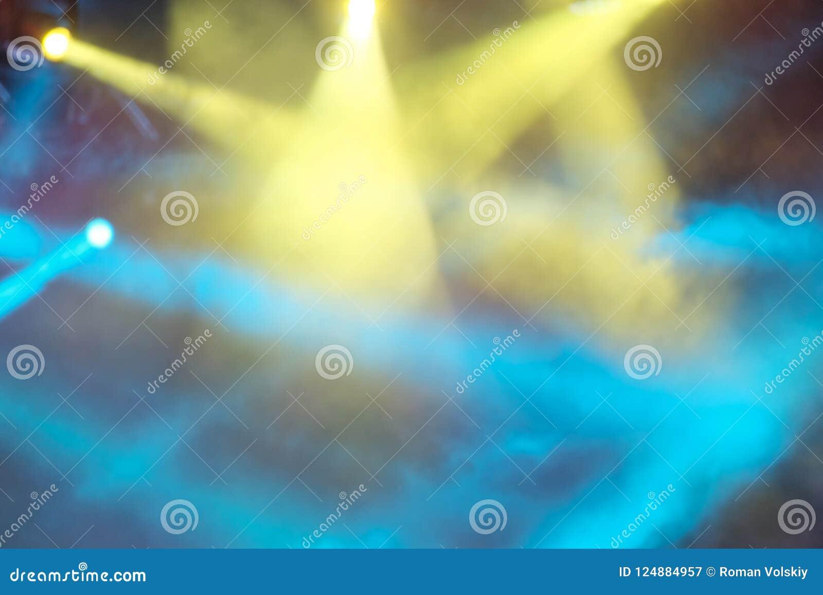 As luzes amarelas e azuis do concerto brilham através do fumo Fundo bonito abstrato de raios de luz coloridos brilhantes blurry