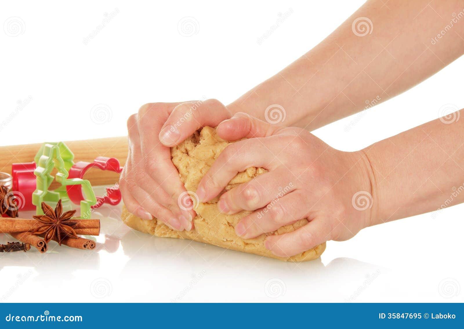 As mãos amassam a massa para cookies do Natal