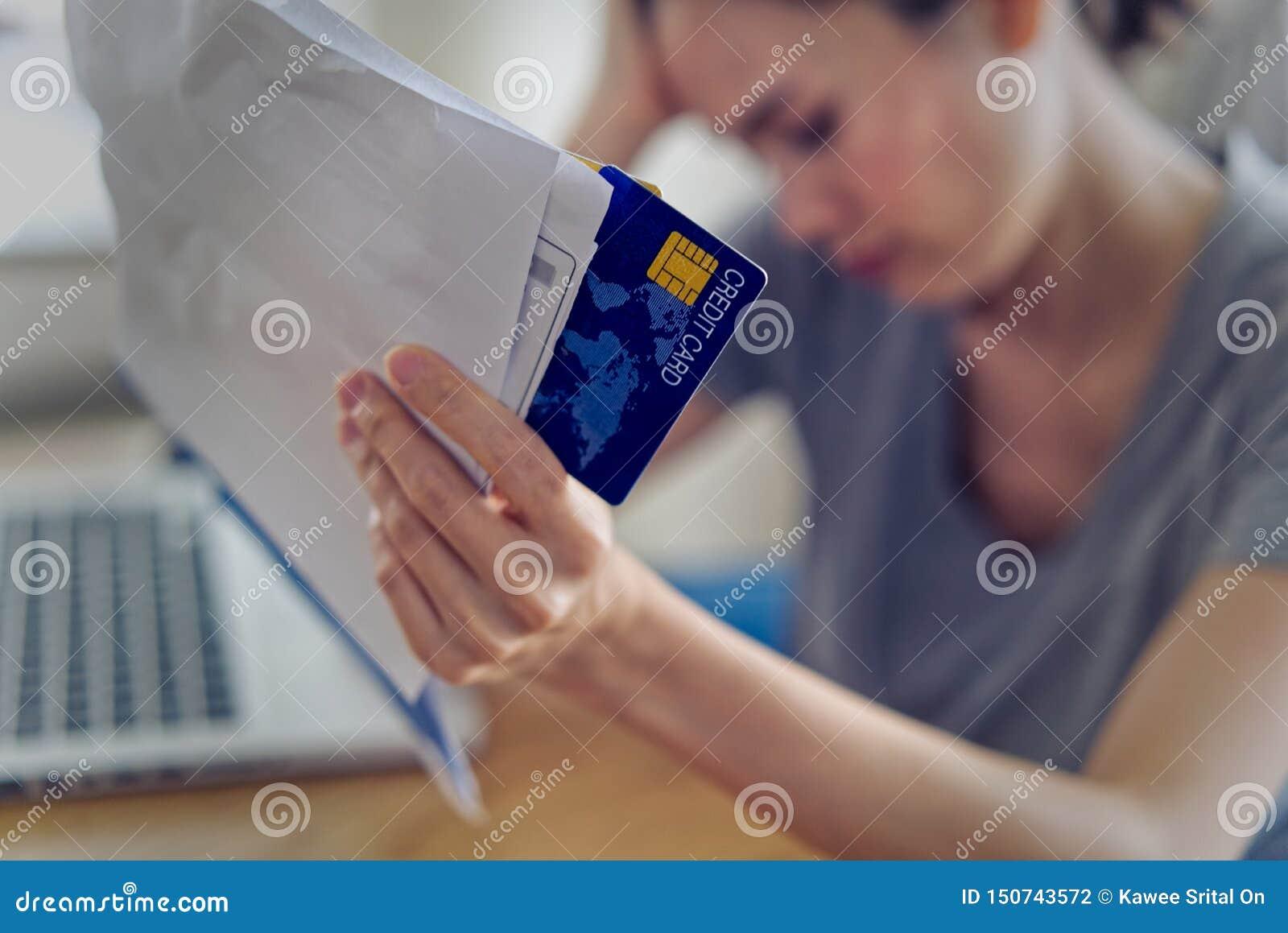 As mãos asiáticas da mulher que guardam o cartão de crédito e as contas preocupam-se sobre o dinheiro do achado para pagar o débi