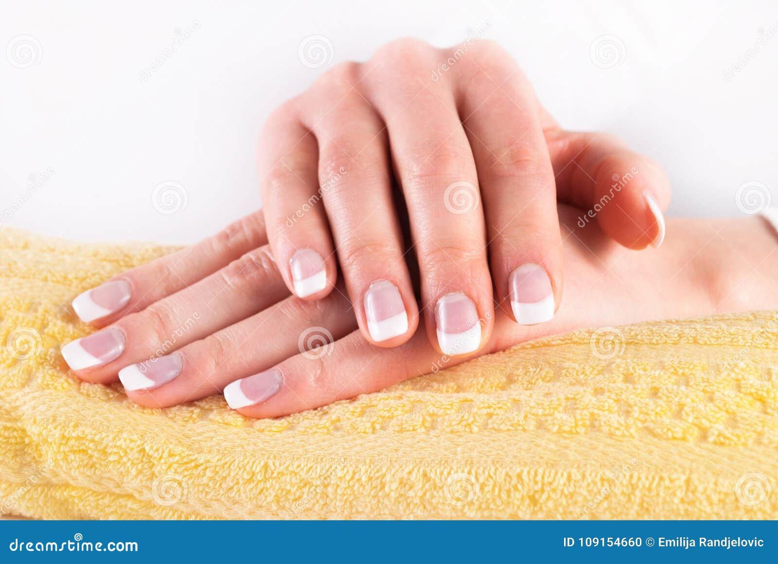 As mãos bonitas da mulher com francês pregam o tratamento de mãos na toalha amarela