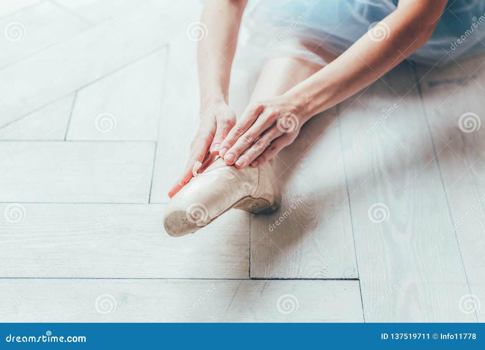 As mãos da bailarina põem sapatas do pointe sobre o pé na classe de dança