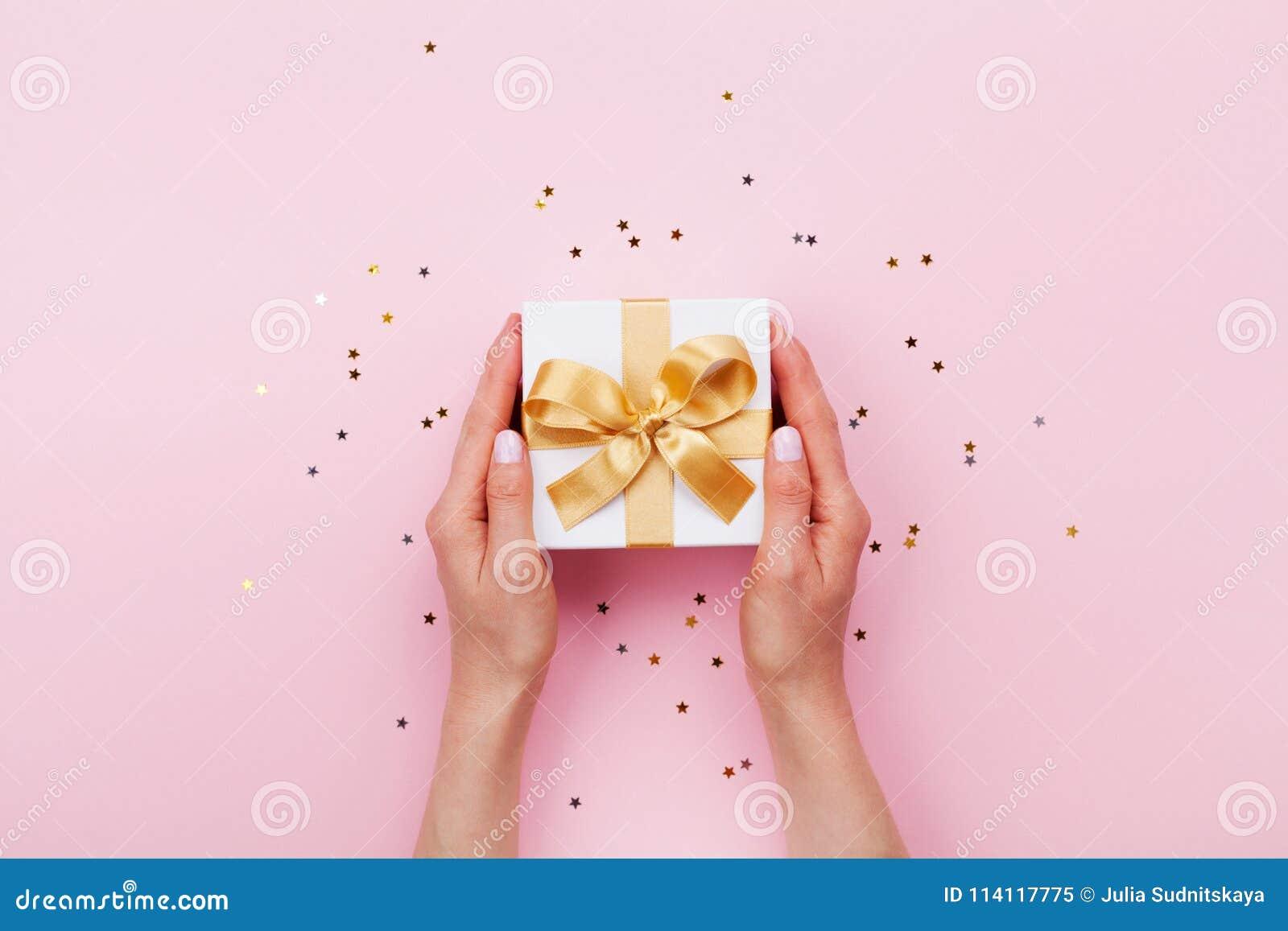 As mãos da mulher que guardam o presente ou a caixa atual decoraram confetes na opinião de tampo da mesa pastel cor-de-rosa Compo