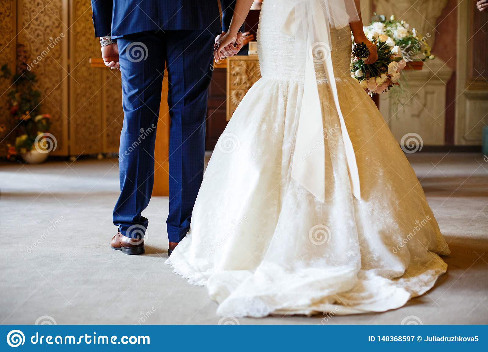As mãos da posse dos noivos na frente do altar
