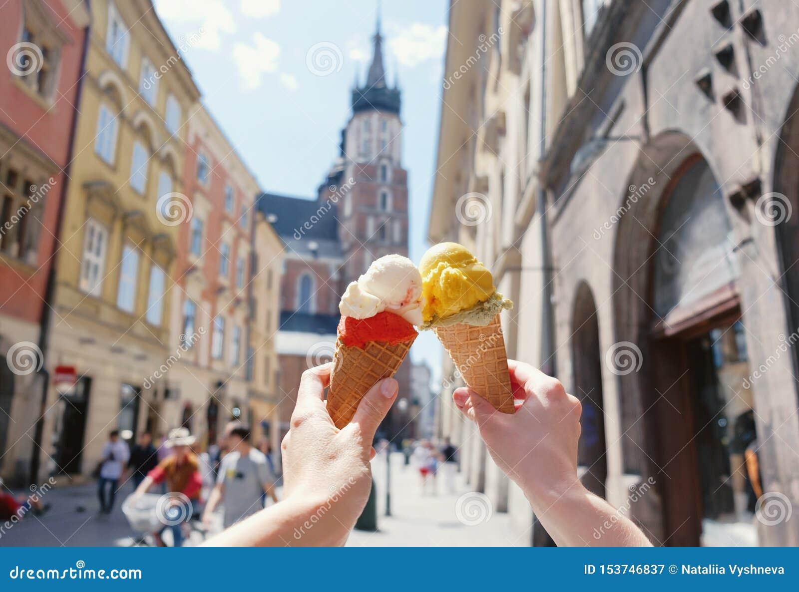 As mãos das mulheres com gelado no fundo da igreja de Mariatsky das vistas da cidade no centro histórico de Krakow, Polônia,