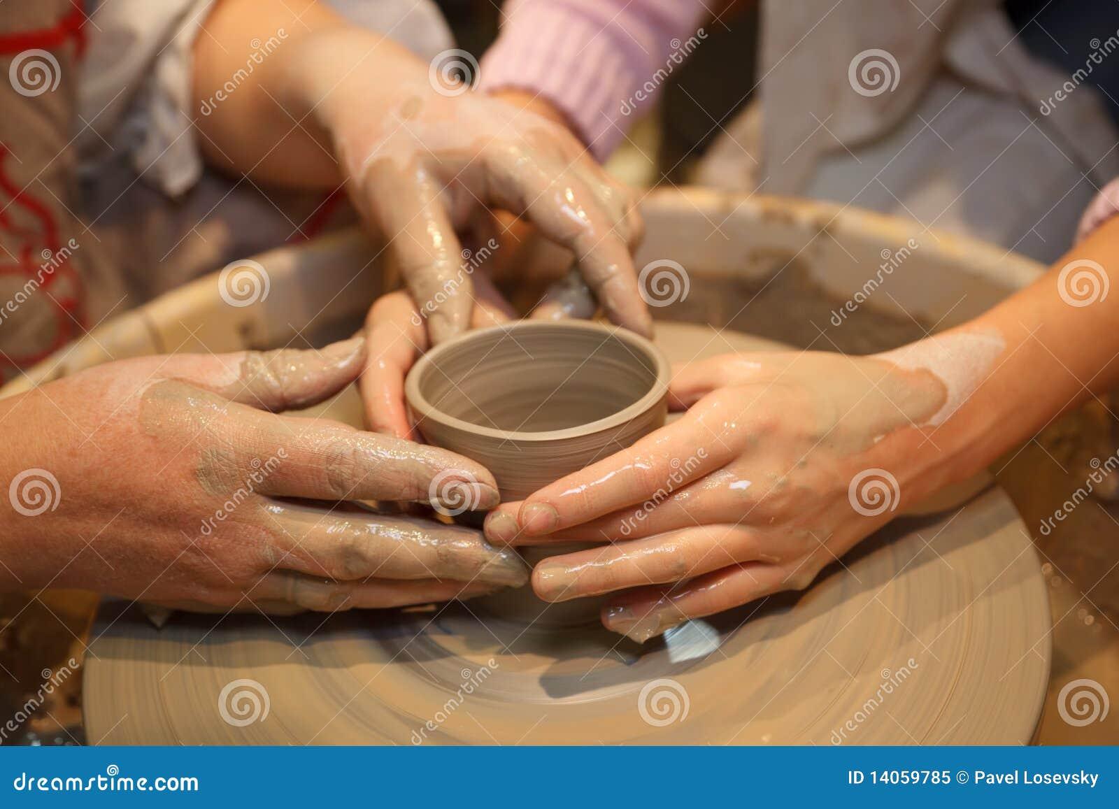 As mãos de dois povos criam o potenciômetro na roda de oleiro