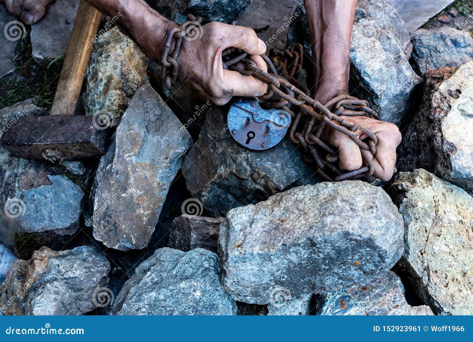 As mãos de um escravo na tentativa de liberar-se O símbolo do trabalho de escravo M?os nas correntes