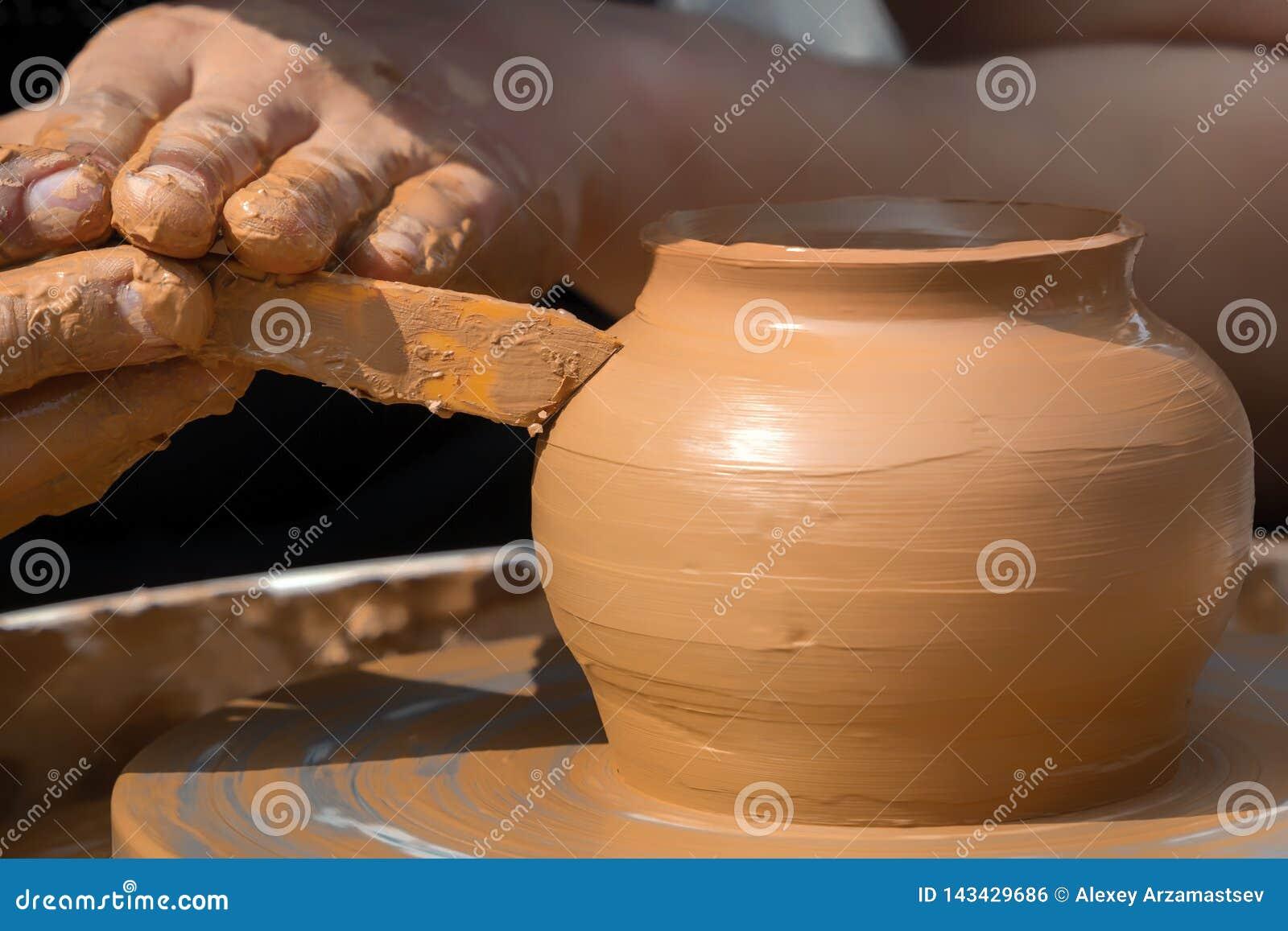 As mãos de um oleiro da rua fazem um potenciômetro de argila em uma roda de oleiro