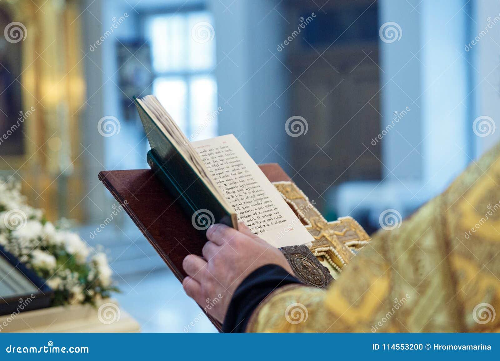 As mãos de um padre ortodoxo, de uma cruz e de um livro de oração