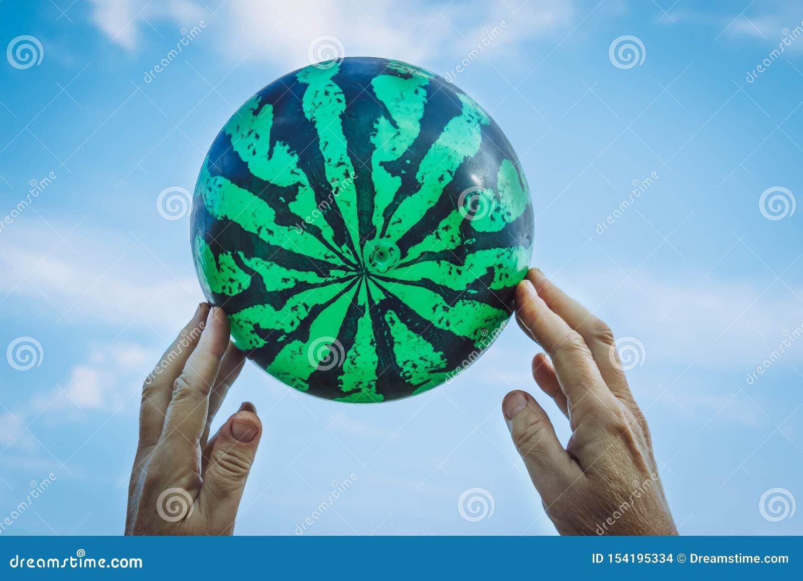 As mãos do ancião que guarda uma bola sob a forma da melancia