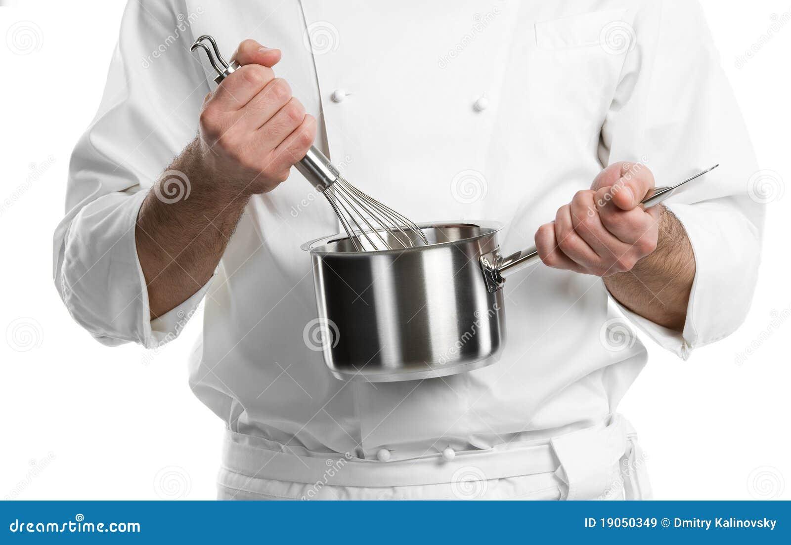 As mãos do cozinheiro chefe com whisk e garimpam