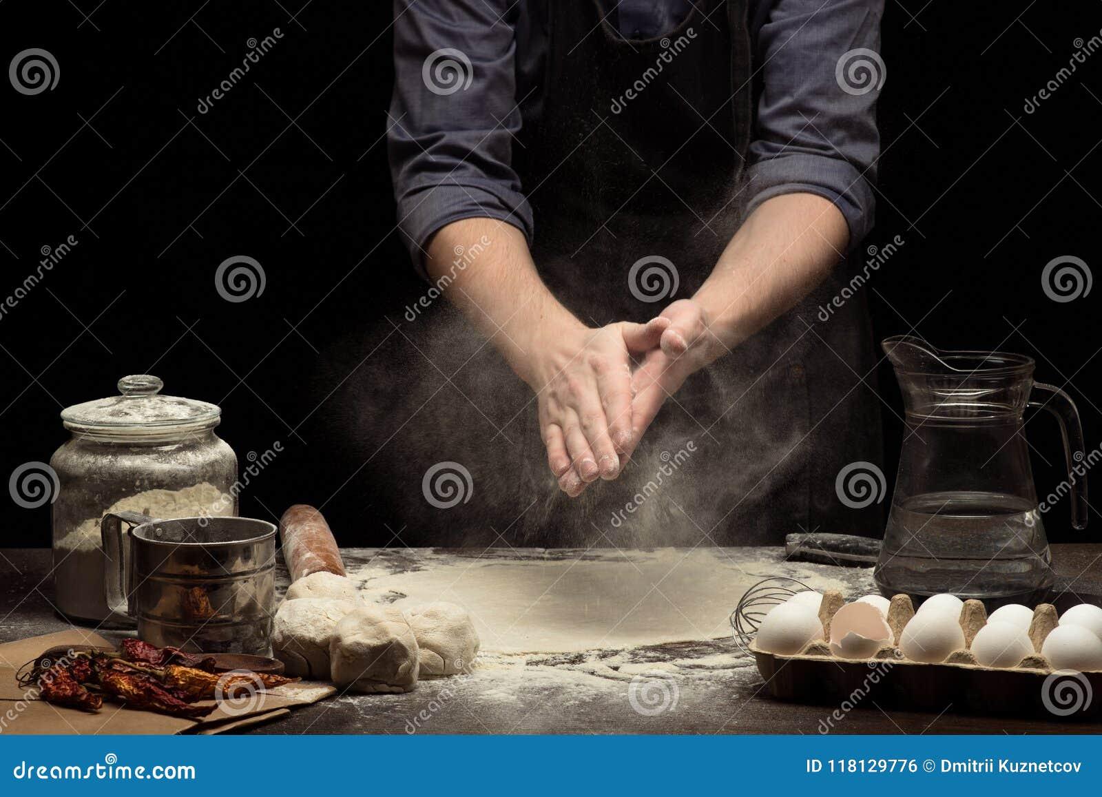 As mãos do cozinheiro chefe estão funcionando com farinha de trigo para fazer uma massa