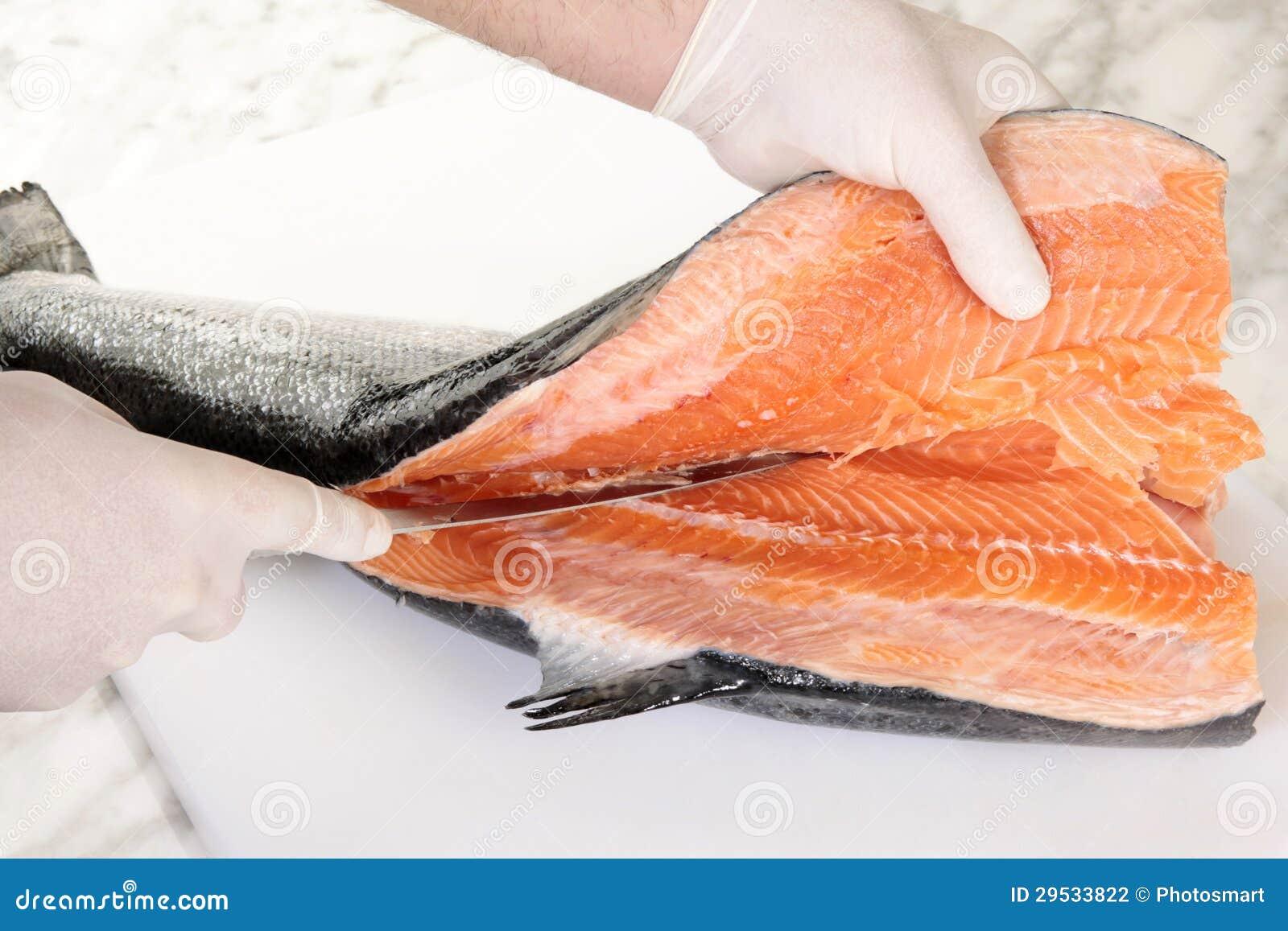 As mãos do cozinheiro chefe que cortam um salmão fresco