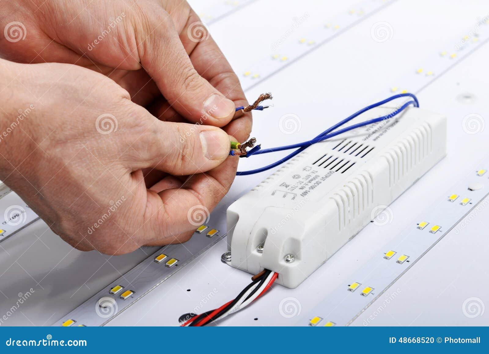 As mãos do eletricista conectam fios da lâmpada conduzida