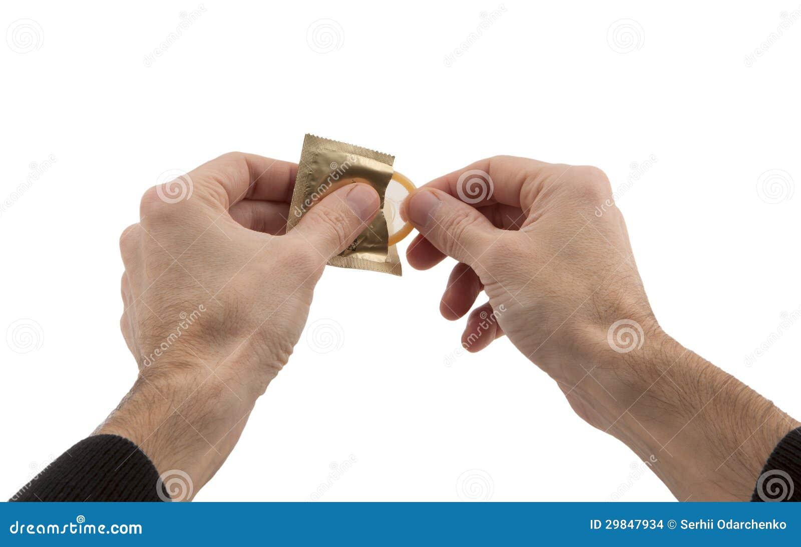 As mãos do homem que abrem o preservativo
