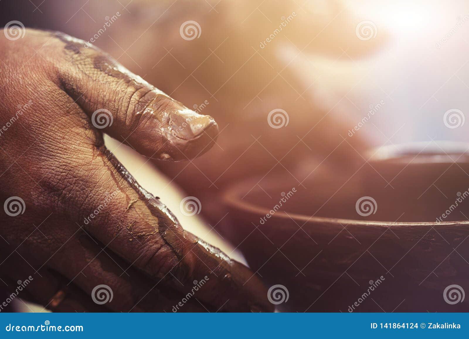 As mãos do oleiro ao trabalhar na roda de oleiro