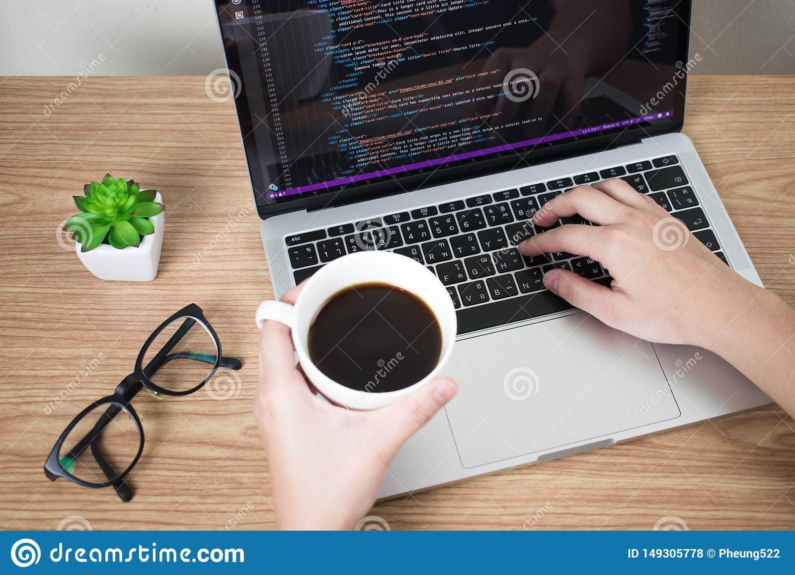 As m?os do programador est?o analisando alguns sistemas e informa??o no tela de computador ao beber o caf? na mesa