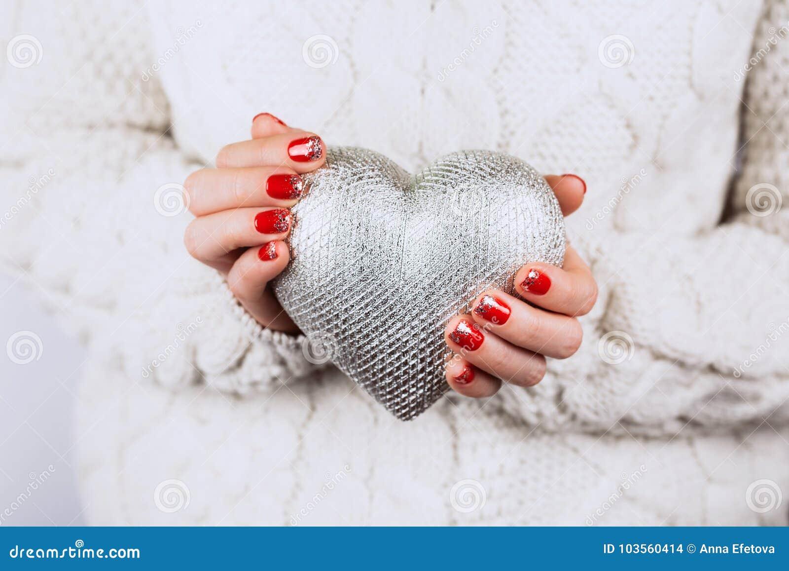 As mãos do ` s da mulher mantêm com cuidado o coração de prata