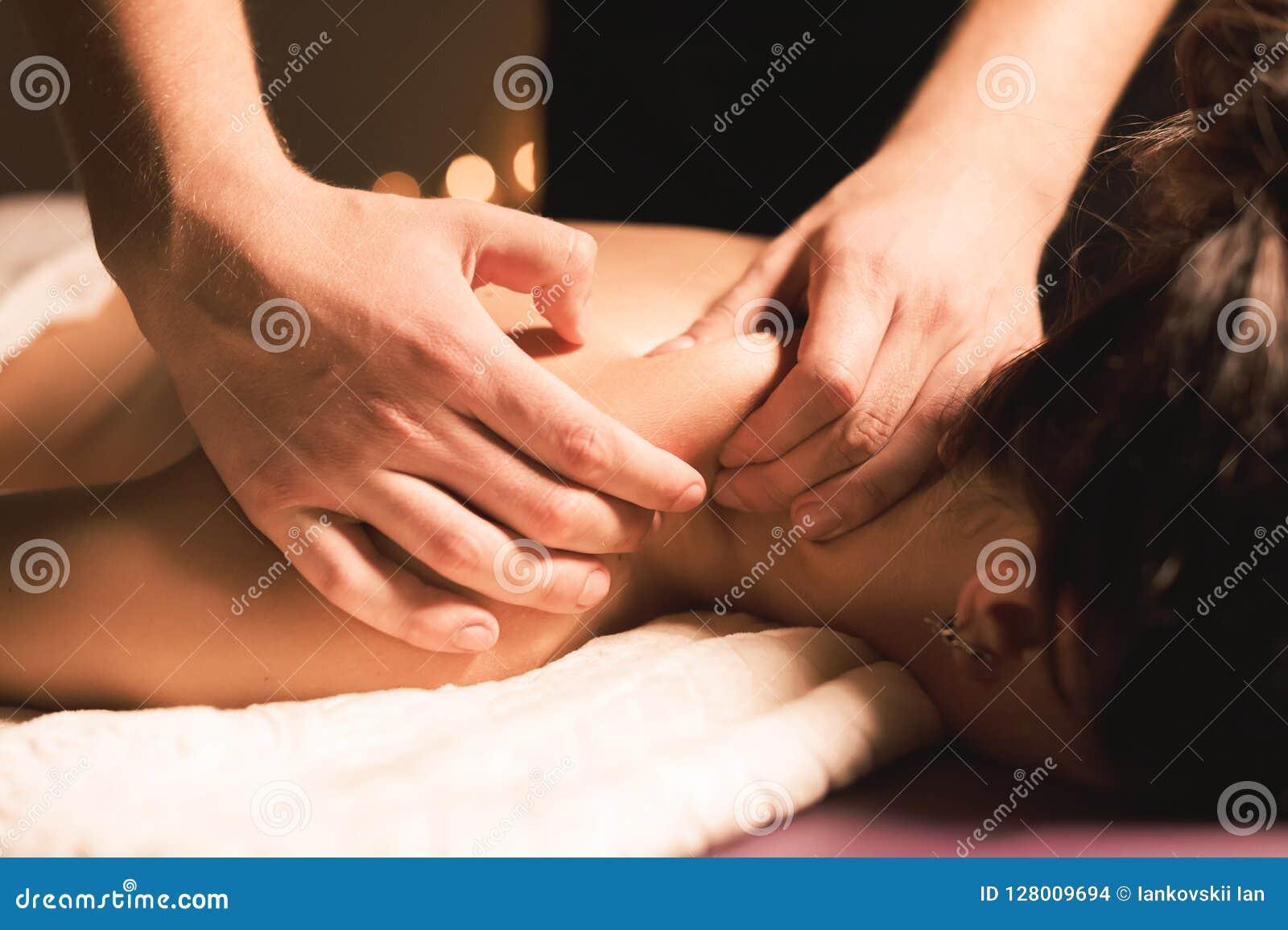 As mãos do ` s dos homens fazem uma massagem terapêutica do pescoço para uma menina que encontra-se em um sofá da massagem em uns