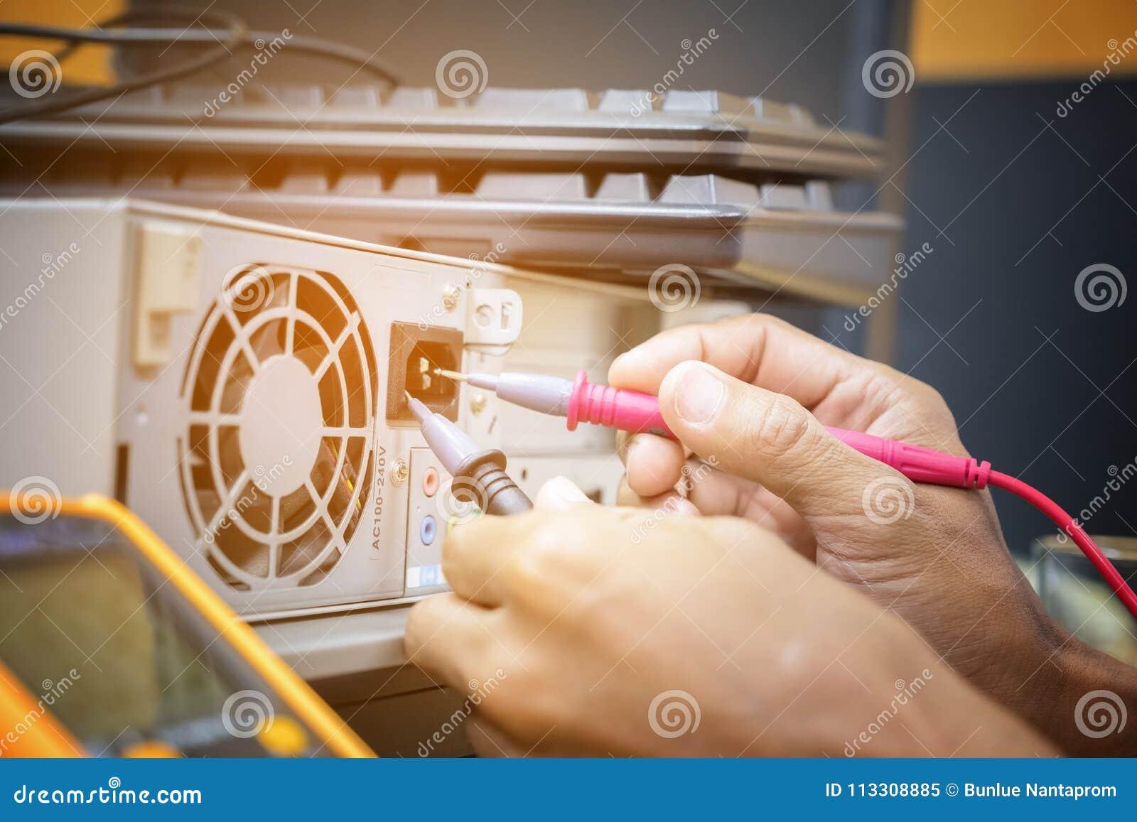 As mãos do técnico da eletrônica usam a verificação da pena do multímetro digital