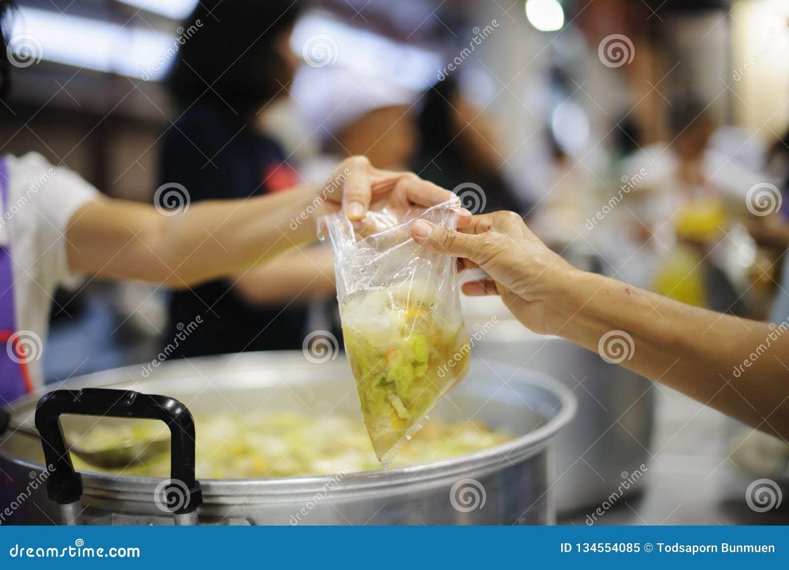 As mãos dos pobres estão esperando doações do alimento para aliviar a fome: conceito da alimentação