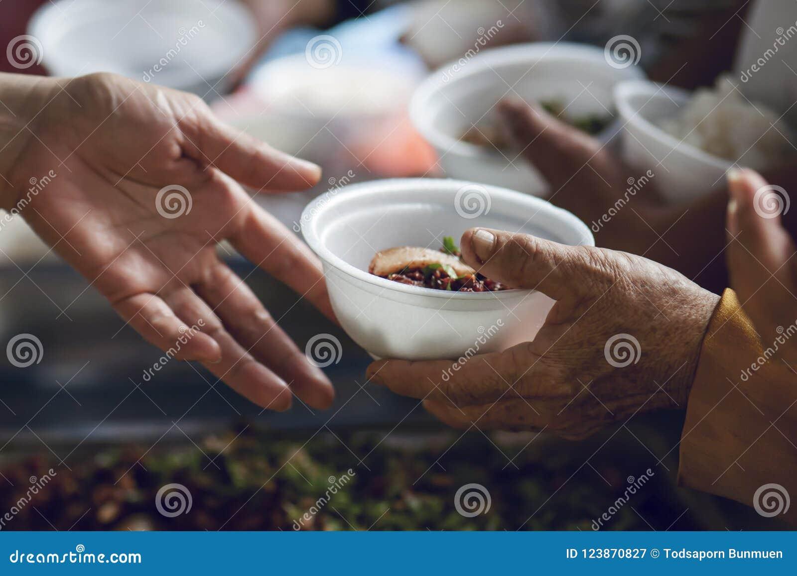 As mãos dos pobres recebem o alimento da parte fornecedora do ` s Conceito da pobreza