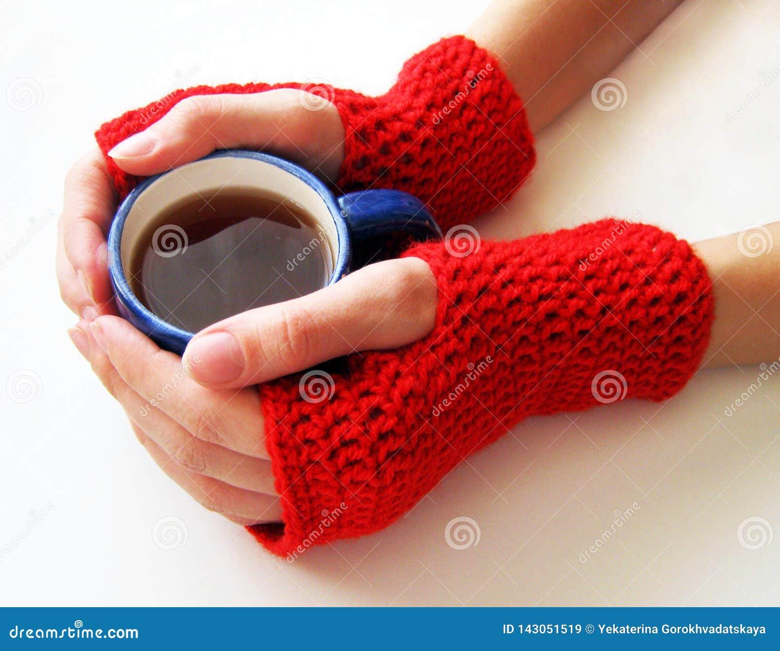 As mãos fêmeas em mitenes vermelhos estão guardando um copo da bebida quente