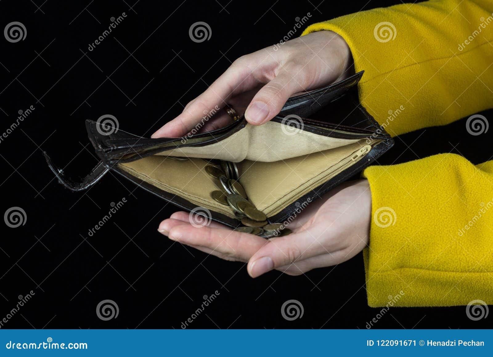 As mãos fêmeas guardam uma bolsa de que derramou moedas, uma finança preta do fundo