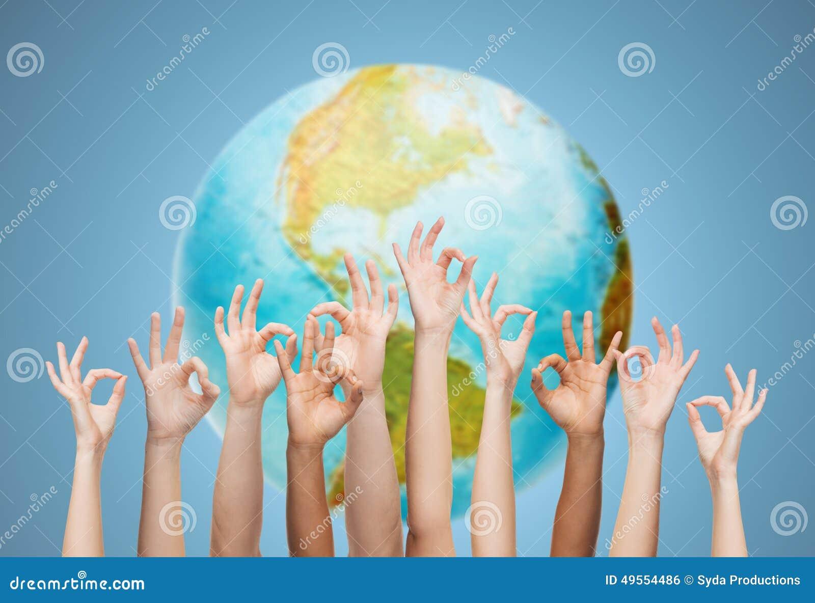 As mãos humanas que mostram está bem assinam sobre o globo da terra