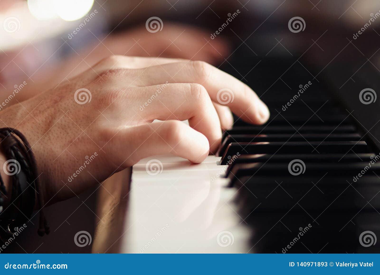 As mãos jogam em um sintetizador musical moderno