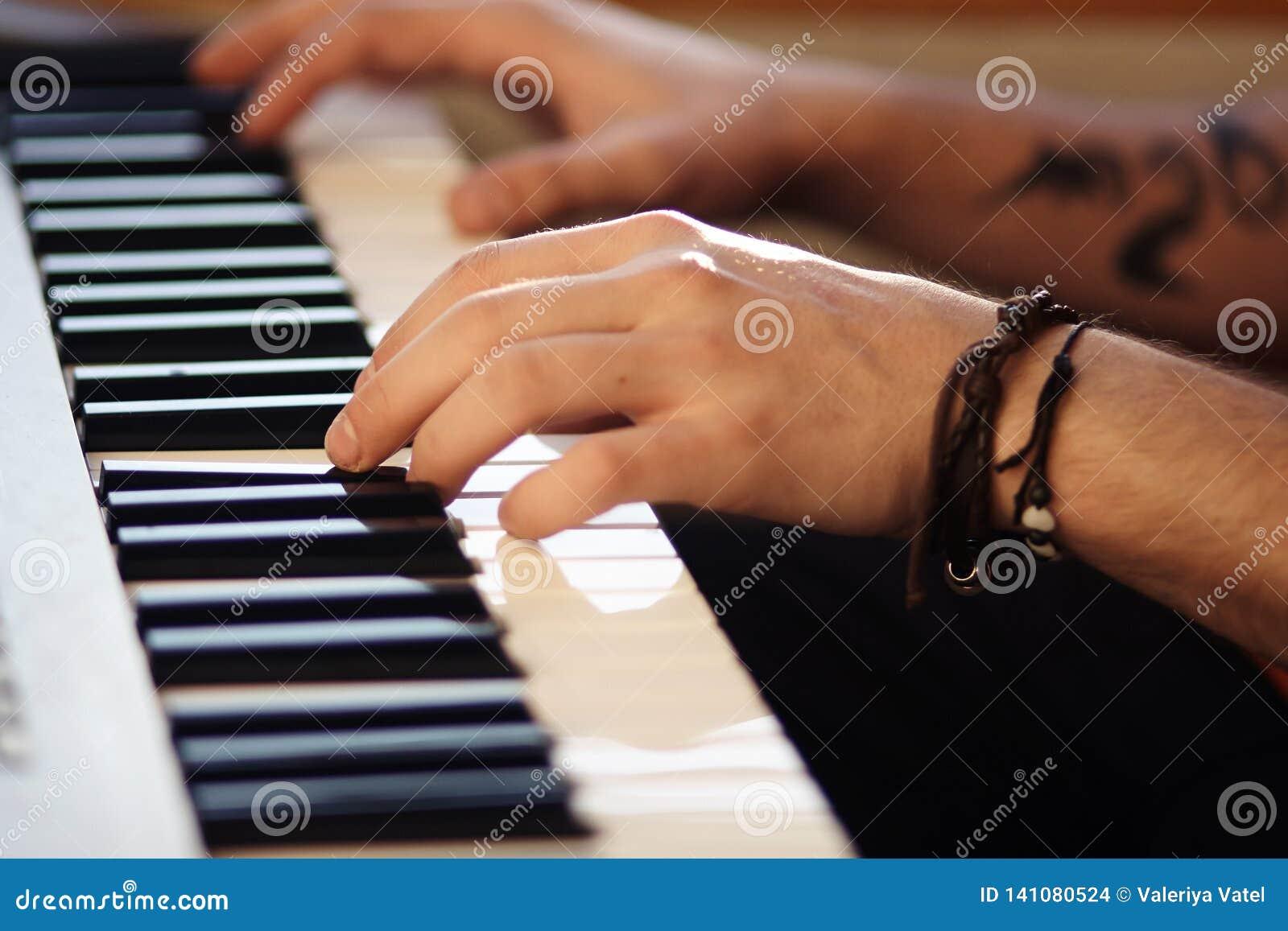 As mãos masculinas bonitas jogam no sintetizador moderno