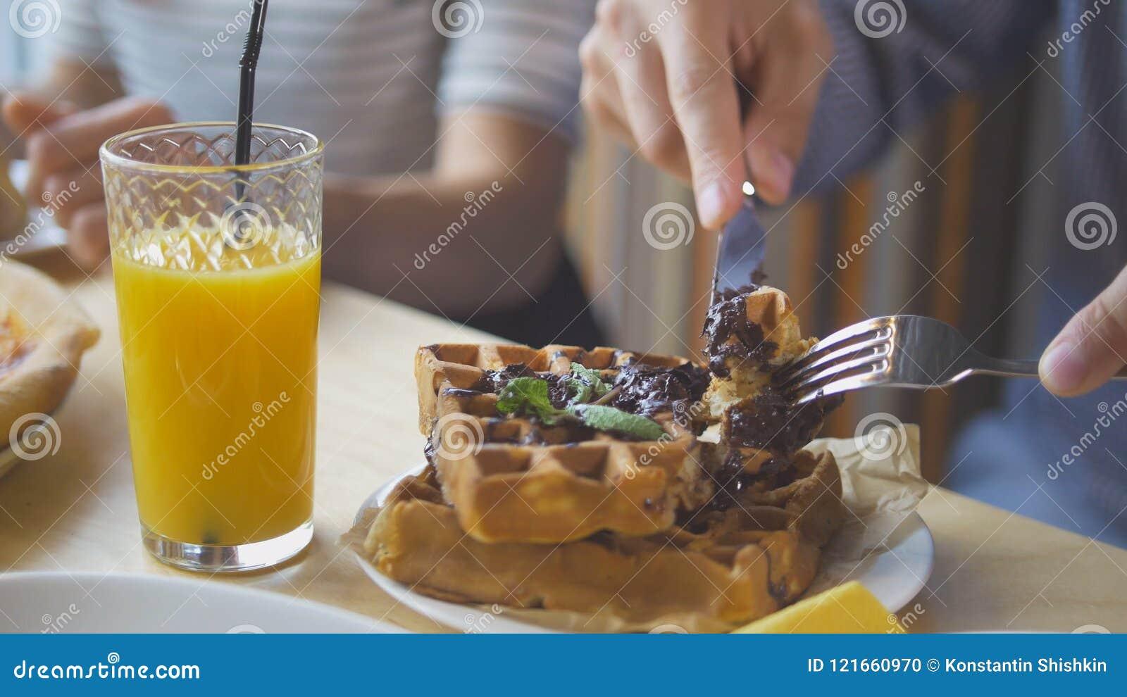 As mãos masculinas cortam waffles belgas saborosos com uma faca e uma forquilha no restaurante