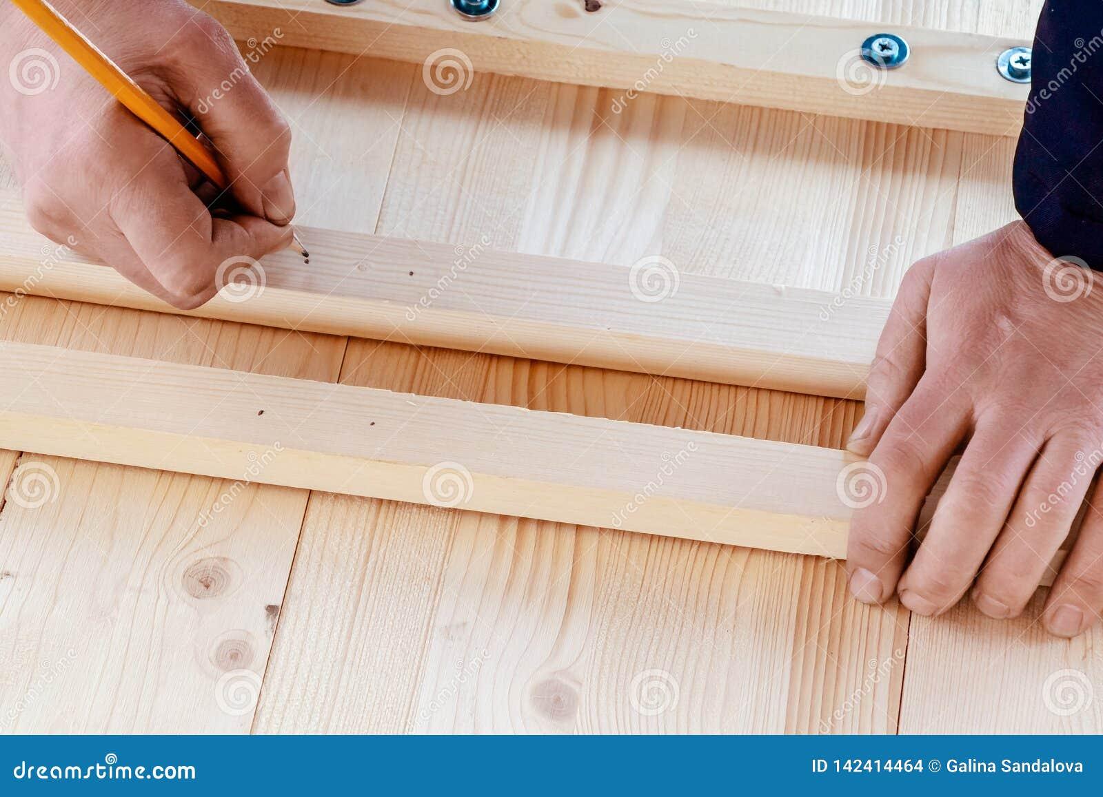 As mãos masculinas estão marcando placas para furos de perfuração para os parafusos