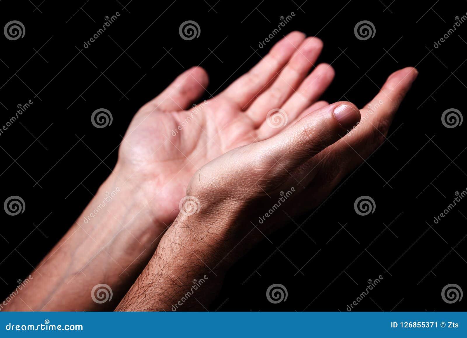 As mãos masculinas que rezam com palmas levantam os braços estendido Fundo preto