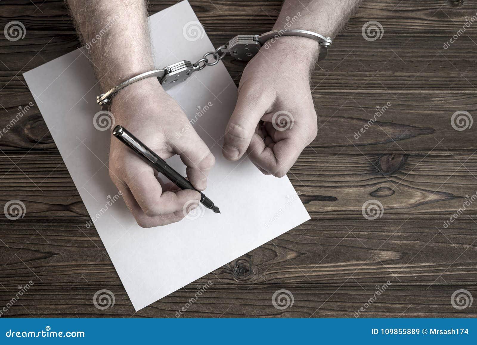 As mãos nas algemas escrevem uma participação no fundo de uma tabela de madeira